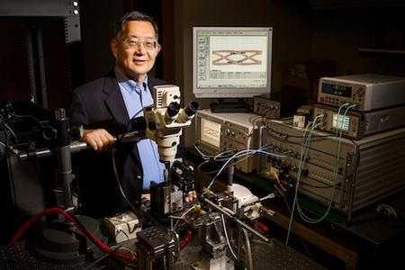 University of Illinois engineer Milton Feng standing next to transistor lasers that could boost computer processor speeds.